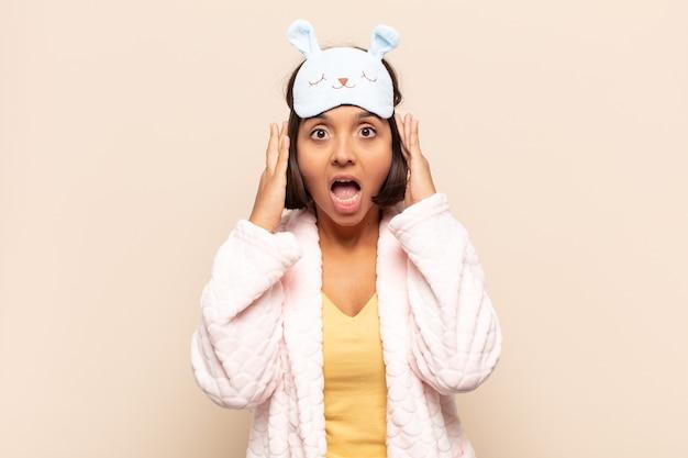Молодая латинская женщина поднимает руки к голове, с открытым ртом, чувствуя себя чрезвычайно удачливой, удивленной, взволнованной и счастливой