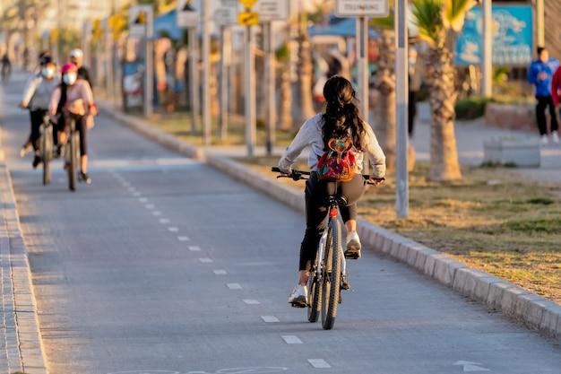 Young latin woman riding a bike on bikeway
