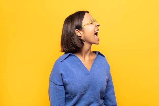 若いラテン女性は猛烈に叫び、積極的に叫び、ストレスと怒りを見て