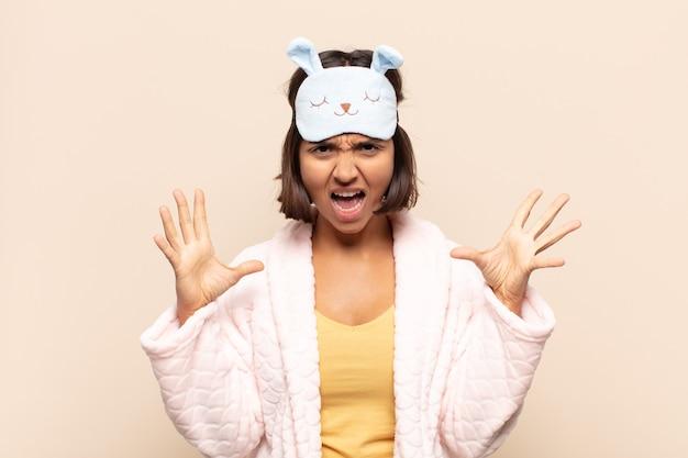 頭の横に手を置いて、パニックや怒り、ショック、恐怖、激怒で叫んでいる若いラテン女性
