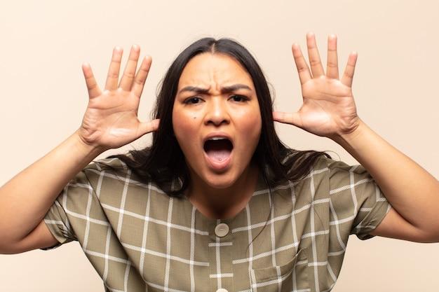 Молодая латинская женщина, кричащая от паники или гнева, шокированная, испуганная или разъяренная, с руками рядом с головой