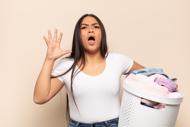 Young latin woman screaming with hands up in the air, feeling furious, frustrated, stressed and upset