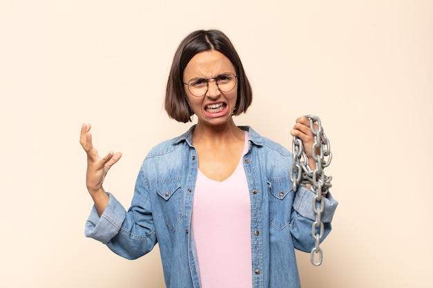 Молодая латинская женщина кричит с поднятыми руками, чувствуя ярость, разочарование, стресс и расстройство