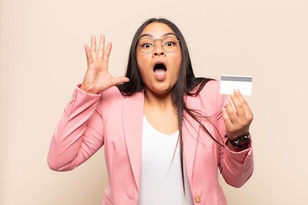 젊은 라틴 여성이 손을 높이 들고 비명을 지르며 화나고, 좌절하고, 스트레스를 받고, 화가 났습니다.