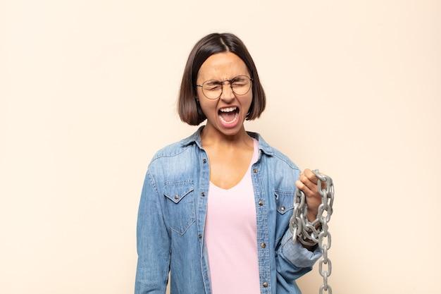 若いラテン女性は積極的に叫び、非常に怒っている、イライラしている、憤慨している、またはイライラしているように見えます。