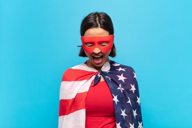 Молодая латинская женщина агрессивно кричит, выглядит очень сердитой, расстроенной, возмущенной или раздраженной, кричит нет