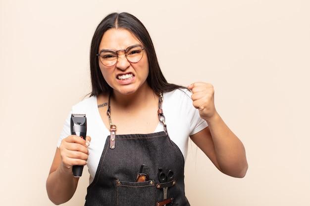 Молодая латинская женщина агрессивно кричит с сердитым выражением лица или со сжатыми кулаками празднует успех