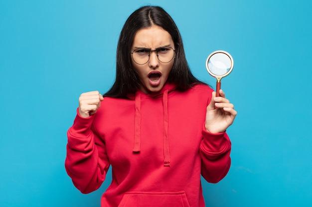 화가 난 표정으로 또는 주먹으로 공격적으로 외치는 젊은 라틴 여자는 성공을 축하합니다
