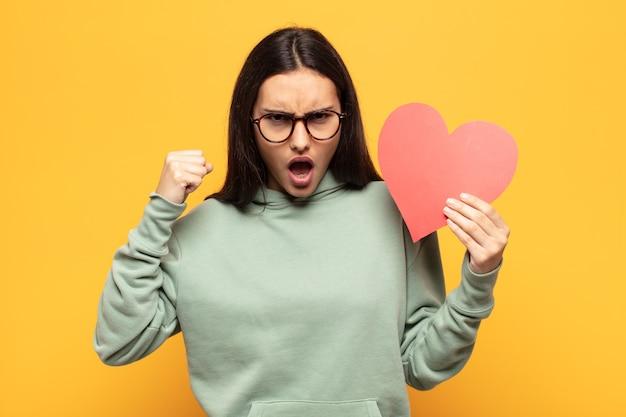 Молодая латинская женщина агрессивно кричит с гневным выражением лица или со сжатыми кулаками празднует успех