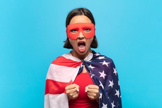 イライラした、欲求不満の、怒った表情とタイトな拳で積極的に叫んでいる若いラテン女性は、激怒を感じています