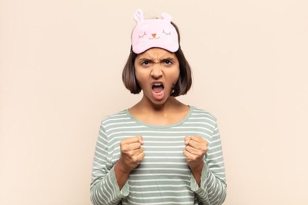 Молодая латинская женщина агрессивно кричит с раздраженным, разочарованным, злым взглядом и сжатыми кулаками, чувствуя ярость