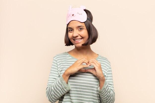 若いラテン女性の笑顔と幸せ、かわいい、ロマンチックな恋を感じ、両手でハートの形を作る