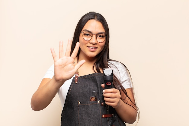 笑顔でフレンドリーに見える若いラテン女性、前に手を前に5または5番を示し、カウントダウン
