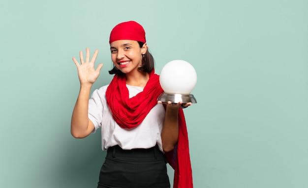 Молодая латинская женщина улыбается и выглядит дружелюбно, показывает номер пять или пятое с рукой вперед, отсчитывая