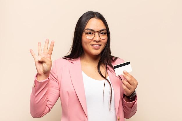 Молодая латинская женщина улыбается и выглядит дружелюбно, показывает номер четыре или четвертый с рукой вперед, отсчитывая