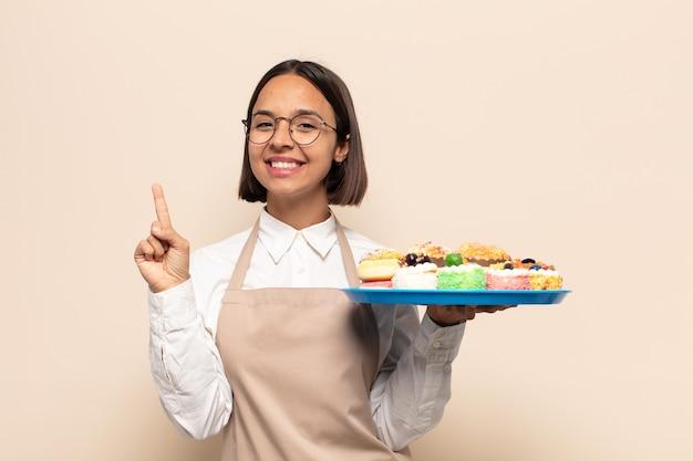Молодая латинская женщина улыбается и выглядит дружелюбно, показывает номер один или первый с рукой вперед, отсчитывая