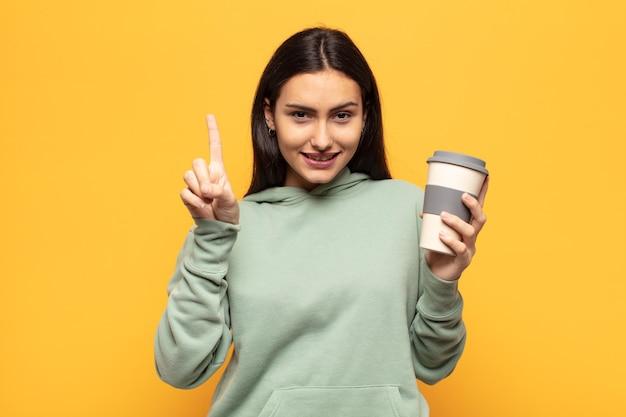 젊은 라틴 여자 웃 고 친절 하 게 찾고, 앞으로 손으로 번호 하나 또는 첫 번째 표시, 카운트 다운
