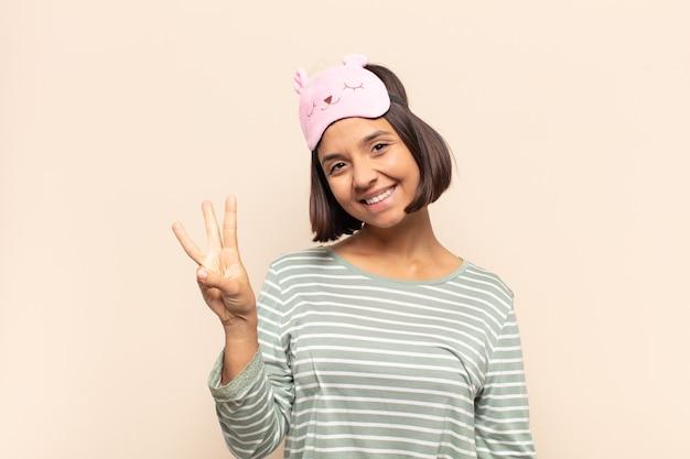 젊은 라틴 여자 웃 고 친절 하 게 찾고, 앞으로 손으로 세 번째 또는 세 번째를 보여주는 카운트 다운