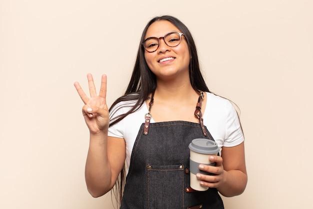 Молодая латинская женщина улыбается и выглядит дружелюбно, показывает номер три или треть рукой вперед, отсчитывая
