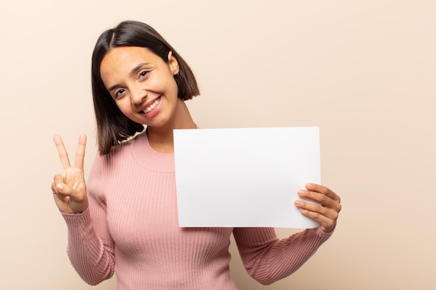 Молодая латинская женщина улыбается и выглядит дружелюбно, показывает номер два или секунду рукой вперед, отсчитывая