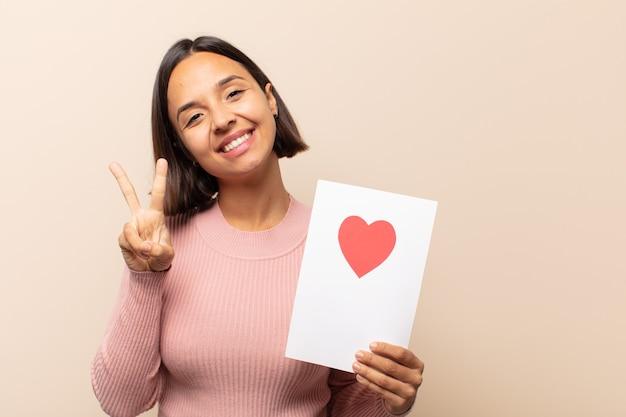 若いラテン女性は笑顔で幸せそうに見え、のんきで前向きで、片手で勝利または平和を身振りで示す