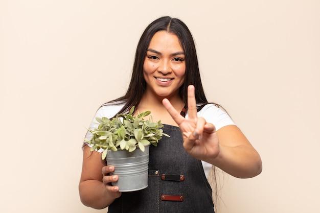 Молодая латинская женщина улыбается и выглядит счастливой, беззаботной и позитивной, показывая победу или мир одной рукой