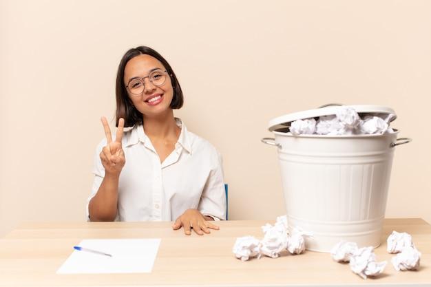 젊은 라틴 여자 웃고 행복하고 평온하고 긍정적 인, 승리 또는 평화를 한 손으로 몸짓