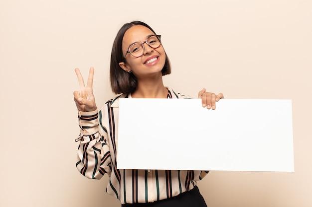 Молодая латинская женщина улыбается и выглядит счастливой, беззаботной и позитивной, жестикулируя победу или мир одной рукой