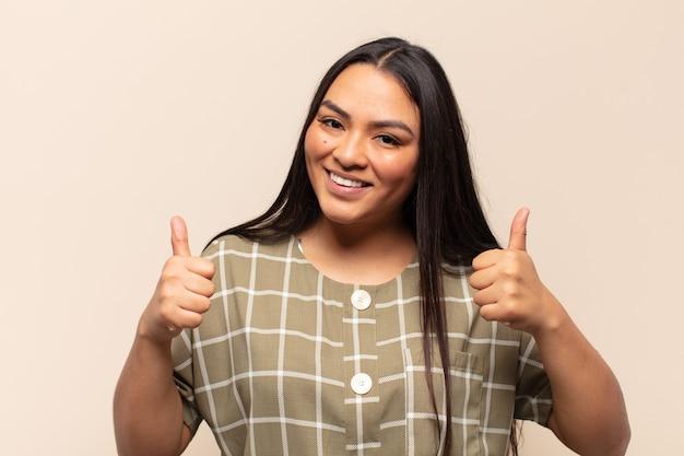 두 엄지 손가락으로 광범위하게 행복하고 긍정적이며 자신감 있고 성공적인 찾고 웃는 젊은 라틴 여자