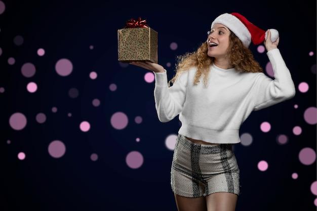 젊은 라틴 여성이 웃고, 손에 선물과 산타클로스 모자를 들고 크리스마스를 축하합니다.