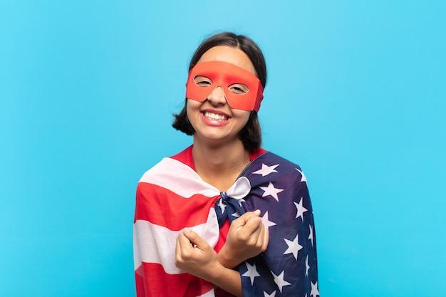 Молодая латинская женщина весело улыбается и празднует со сжатыми кулаками и скрещенными руками, чувствуя себя счастливой и позитивной