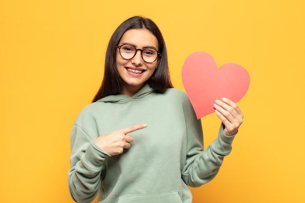 若いラテン女性は元気に笑って、幸せを感じ、横と上を指して、コピースペースにオブジェクトを表示
