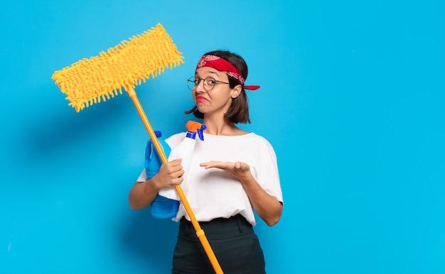 유쾌하게 웃고, 행복감을 느끼고 손바닥으로 복사 공간에 개념을 보여주는 젊은 라틴 여자