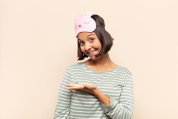 Молодая латинская женщина весело улыбается, чувствует себя счастливой и показывает концепцию в копировальном пространстве ладонью