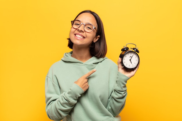 Young latin woman smiling cheerfully, feeling happy and pointing to the side and upwards, showing object in copy space