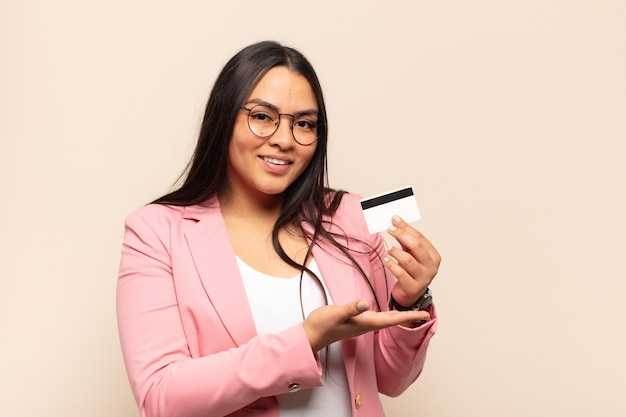 Young latin woman smiling cheerfully, feeling happy and showing a concept in copy space with palm of hand