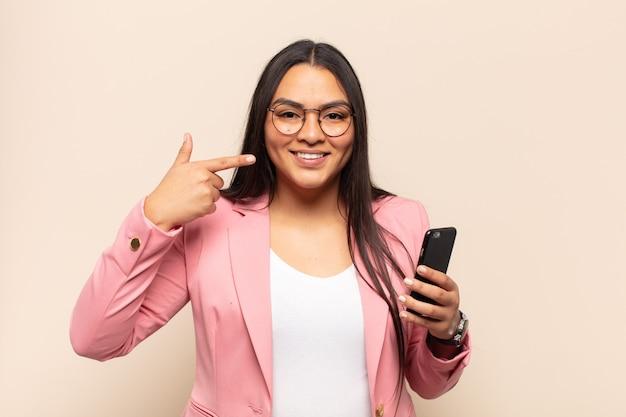 자신의 넓은 미소, 긍정적이고 편안하고 만족스러운 태도를 자신있게 가리키는 젊은 라틴 여자