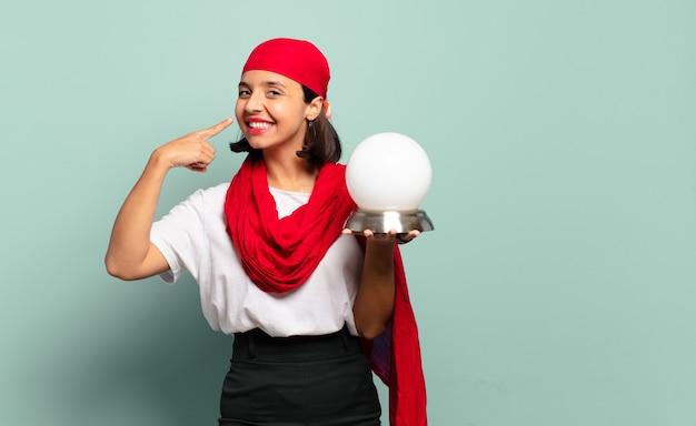 自信を持って微笑む若いラテン女性が、自分の広い笑顔、ポジティブ、リラックス、満足した態度を指し示す