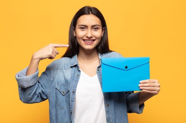 自信を持って笑顔の若いラテン女性は、自分の広い笑顔、前向きで、リラックスした、満足のいく態度を指しています