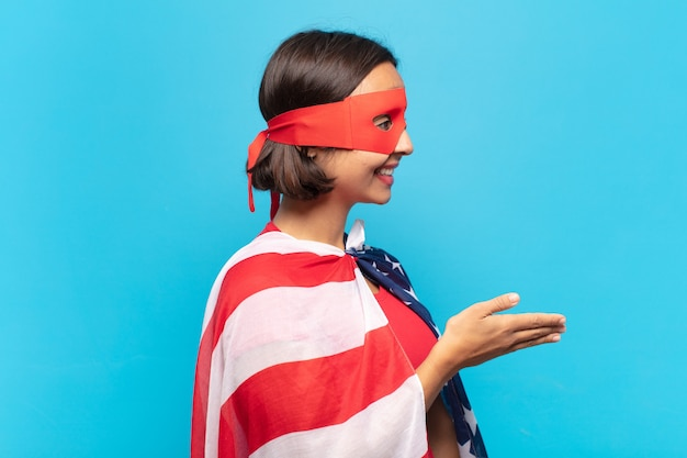 笑顔、あなたに挨拶し、成功した取引、協力の概念を閉じるために握手を提供する若いラテン女性