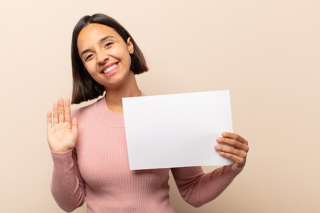 若いラテン女性は幸せにそして元気に笑って、手を振って、あなたを歓迎して挨拶するか、さようならを言っています