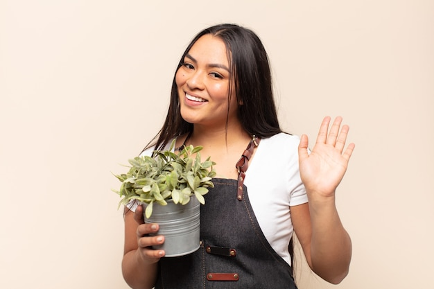 Молодая латинская женщина счастливо и весело улыбается, машет рукой, приветствует и приветствует вас или прощается