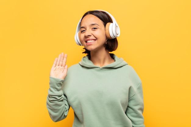 若いラテン女性は幸せにそして元気に笑って、手を振って、あなたを歓迎し、挨拶します