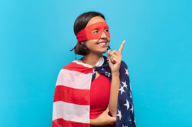 幸せに笑って横向きに、疑問に思ったり、考えたり、アイデアを持っている若いラテン女性