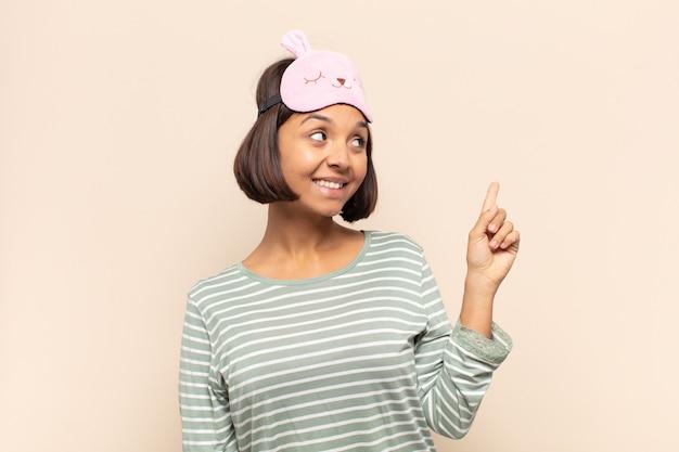 Молодая латинская женщина счастливо улыбается и смотрит в сторону, задается вопросом, думает или имеет идею