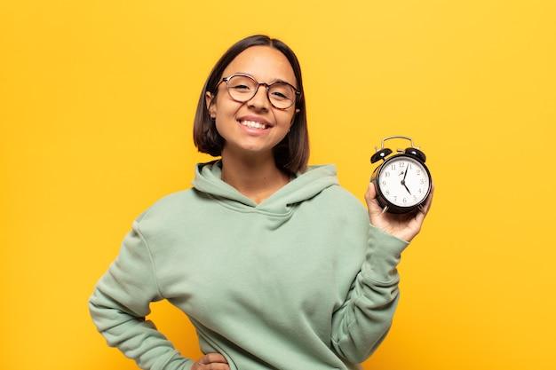 엉덩이와 자신감, 긍정적이고 자랑스럽고 친절한 태도에 손으로 행복하게 웃는 젊은 라틴 여자
