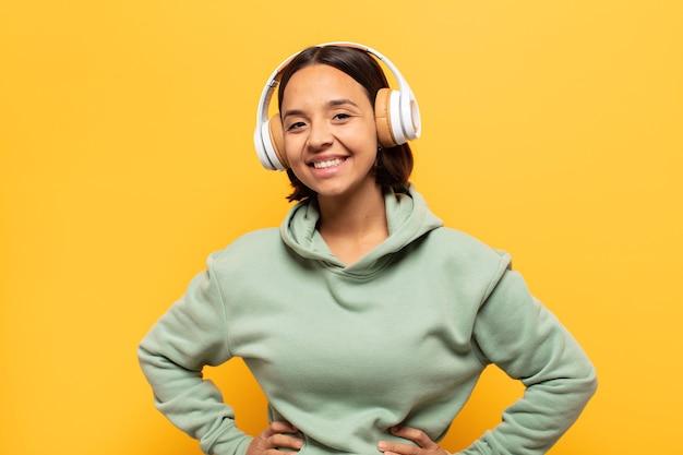 腰に手を当てて幸せそうに笑っている若いラテン女性と自信を持って、前向きで、誇りに思って、フレンドリーな態度