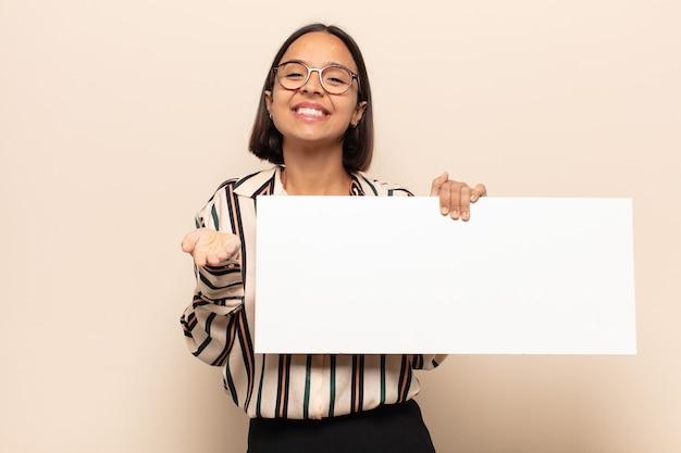 Молодая латинская женщина счастливо улыбается с дружелюбным, уверенным, позитивным взглядом, предлагая и показывая объект или концепцию