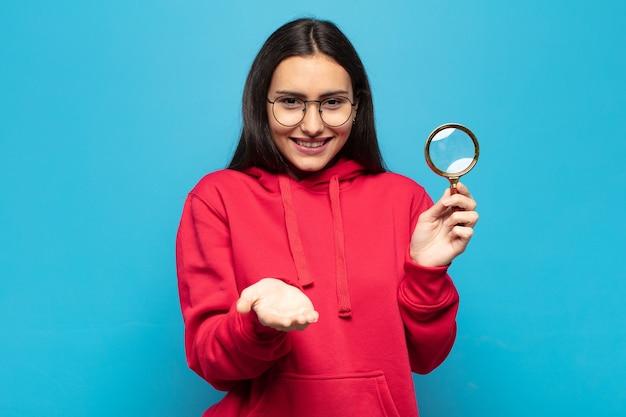 친절하고 자신감 있고 긍정적 인 표정으로 행복하게 웃고 물건이나 개념을 제공하고 보여주는 젊은 라틴 여자