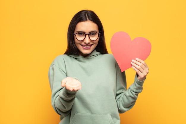 フレンドリーで自信に満ちた、前向きな表情で幸せそうに笑って、オブジェクトやコンセプトを提供し、示すラテン系の若い女性
